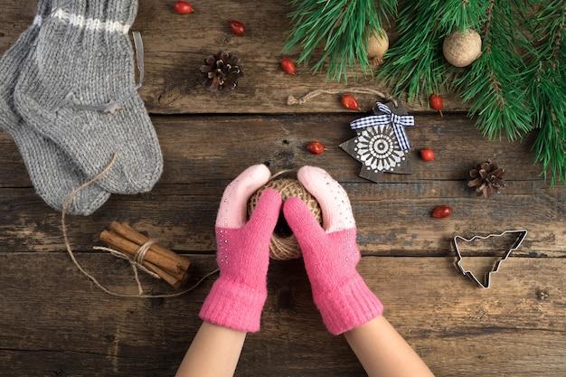 Les mains de l'enfant tiennent une boule de fil parmi les attributs de noël.