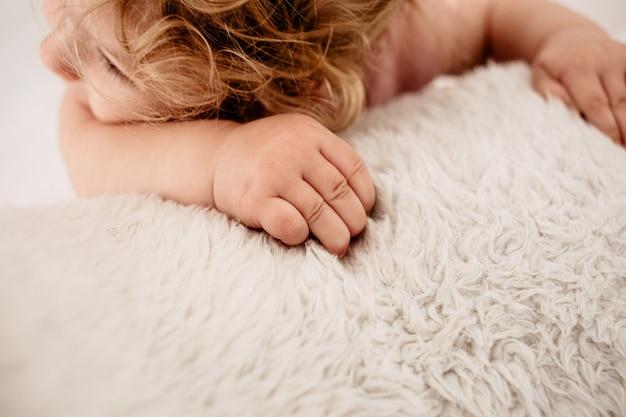 Les mains de l'enfant tiennent une couverture tricotée