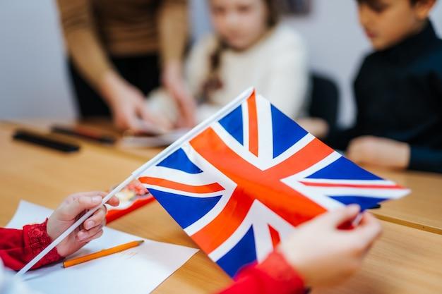 Les mains de l'enfant tiennent le drapeau britannique de l'angleterre