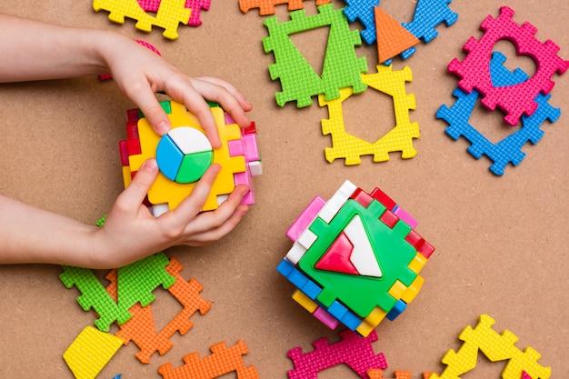 Les mains de l'enfant tiennent des trieurs de puzzle sous forme de cubes