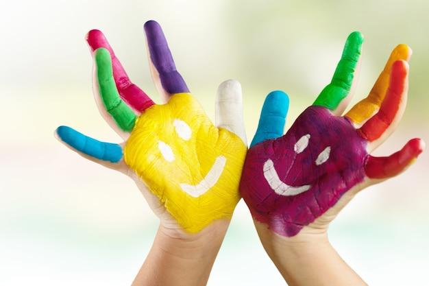 Mains enfantines peintes colorées avec des visages de griffonnage sur eux