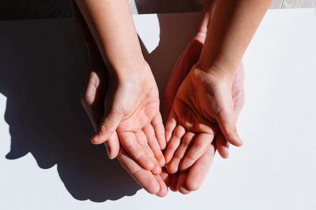 Les mains des enfants et des adultes de la famille ont un cœur entre leurs mains. isoler