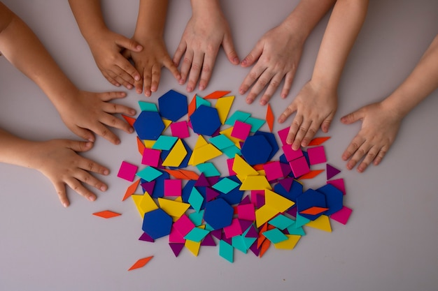 Mains d'enfants d'âge préscolaire jouant avec des blocs colorés