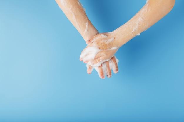 Mains d'enfants dans une mousse de savon, sur bleu, vue de dessus.