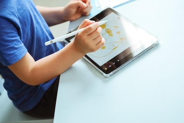Mains d'enfants dessinant avec un stylo numérique sur l'image de la tablette avec espace de copie photo de haute qualité