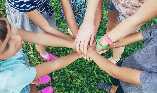 Les mains des enfants ensemble sur un fond d'herbe.