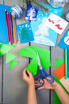 Les mains des enfants fabriquent des jouets de noël faits à la main en carton. diy pour enfants.