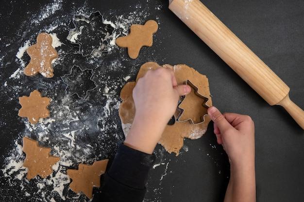 Les mains des enfants font des biscuits au pain d'épice du nouvel an sur une table en bois. faire des biscuits avec un emporte-pièce. concept de nouvel an et de noël.