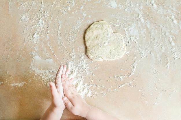 Les mains des enfants font de la pâte