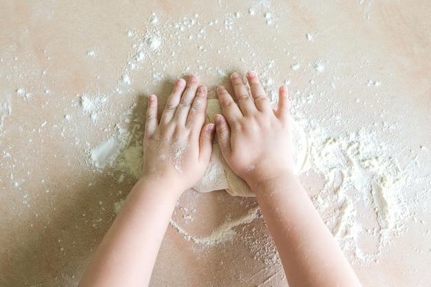 Les mains des enfants font la pâte