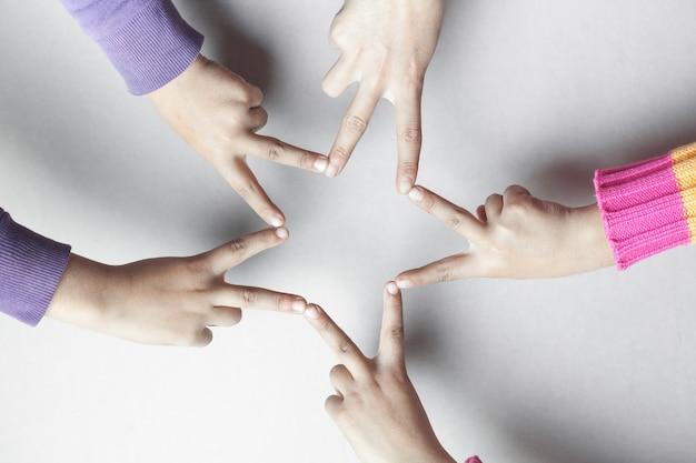 Les mains des enfants forment une étoile.