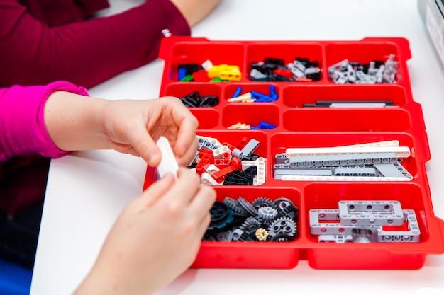 Les mains des enfants jouent avec des blocs lego colorés sur table blanche