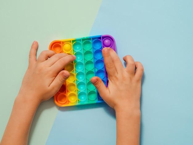 Les mains des enfants jouent avec un jouet popit sur fond bleu
