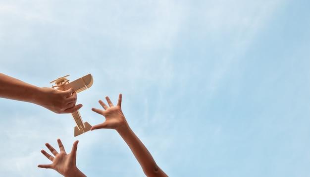 Mains d'enfants et mains de père jouant jouet d'avion en bois sur un beau ciel