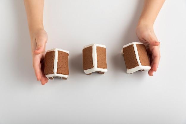 Mains d'enfants et maisons en pain d'épice sur la vue de dessus de fond blanc.
