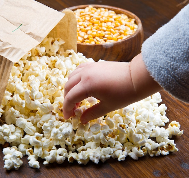 Mains d'enfants mangeant du pop-corn