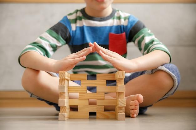 Les mains des enfants ont fait un toit sur une maison en blocs de bois de leurs propres mains, journée internationale de la famille, familles d'accueil, éloignement social et concept d'assurance habitation.