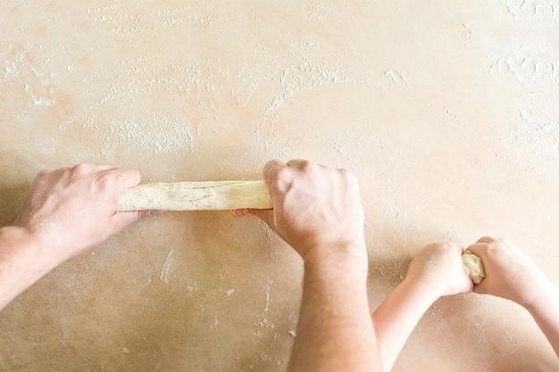 Les mains des enfants et des papas font de la pâte crue