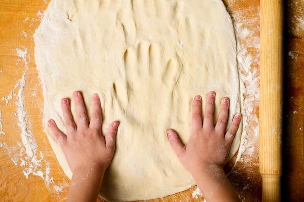 Les mains des enfants sur la pâte, sculpter les empreintes de mains.