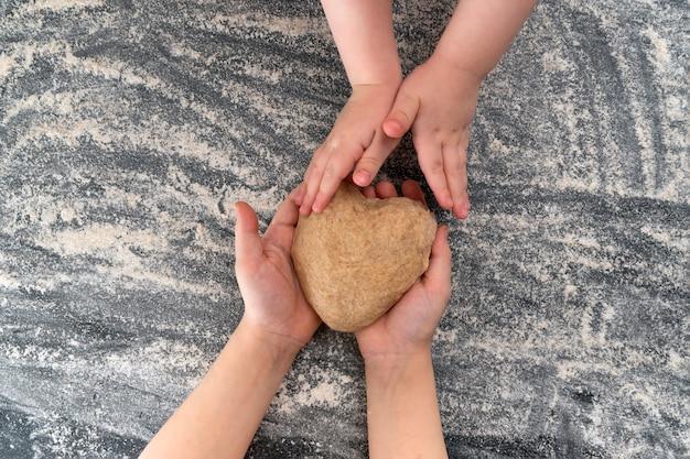 Les mains des enfants avec de la pâte sur la table à la cuisine à domicile
