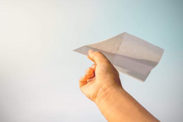 Les mains des enfants ramassent des avions en papier.