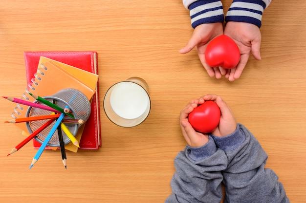 Mains d'enfants tenant coeur rouge et cahier avec crayon de couleur et lait sur table en bois