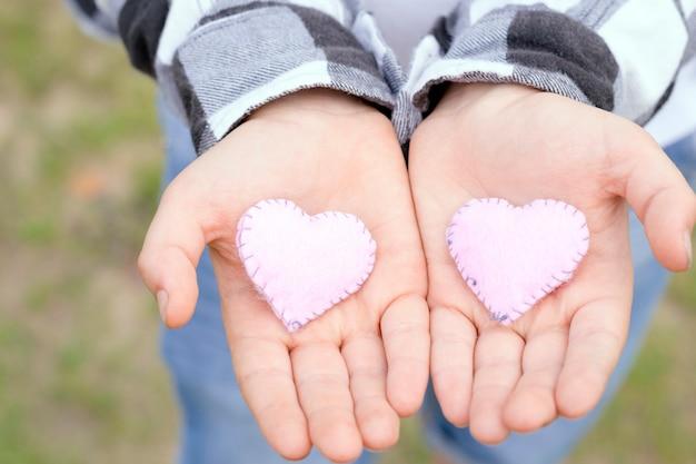 Mains d'enfants tenant des coeurs à la main