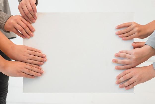 Mains d'enfants tenant du papier