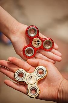 Mains d'enfants tenant des fileuses fidgqet. jouet tendance et populaire pour enfants et adultes.