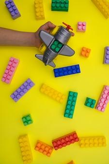 Les mains des enfants tiennent un avion composé de pièces de créateurs sur fond jaune.