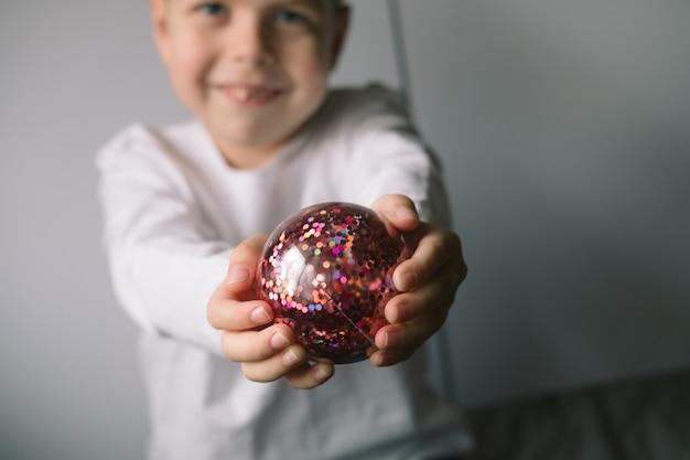 Les mains des enfants tiennent un bal du nouvel an rouge brillant, en gros plan. concept de fête familiale pour noël et nouvel an.