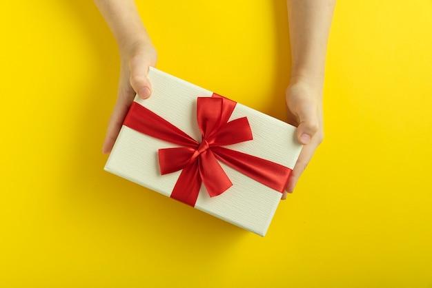 Les mains des enfants tiennent un cadeau sur fond jaune. vue de dessus. coffret cadeau dans les mains des enfants.