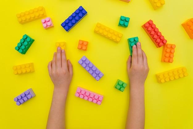 Les mains des enfants tiennent les détails du constructeur sur fond jaune.