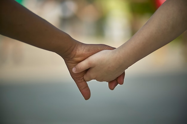 Des mains d'enfants tremblantes, l'une au teint caucasien ou blanc, l'autre noire. symbole d'inertie et d'égalité entre les races.
