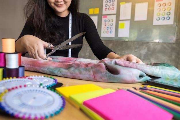 Mains entaille tailleur ciseaux chiffon chiffon coupant un morceau de tissu (concept designer de mode).
