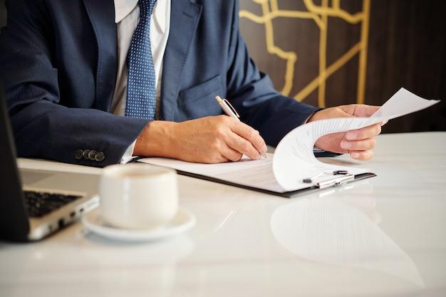 Mains de l'entrepreneur signant des documents et des contrats lors d'un café du matin
