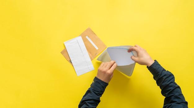 Mains avec enveloppe en papier prêt à envoyer une lettre