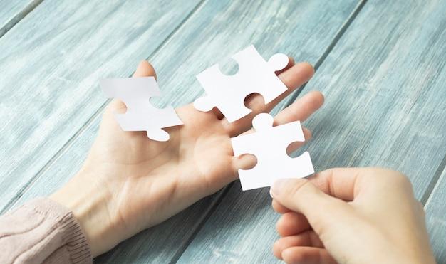 Mains essayant d'assembler deux pièces de puzzle