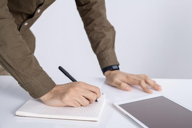 Mains d'étudiant avec un stylo sur une page vierge du cahier de réflexion d'idées tout en écrivant le plan du projet