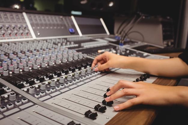 Mains d'une étudiante à l'aide d'une table de mixage sonore