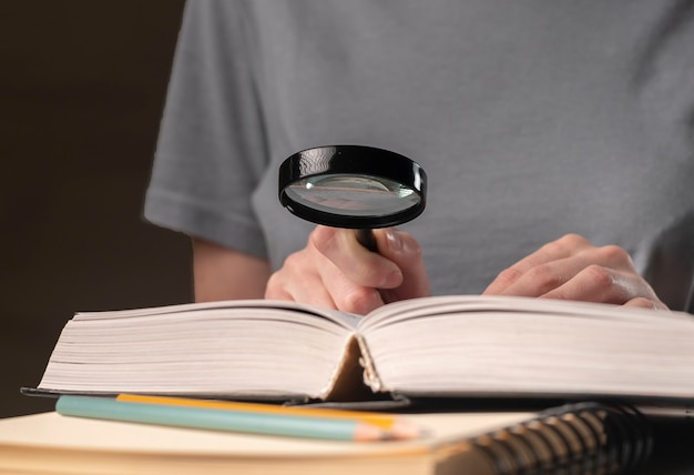 Les mains des étudiantes se bouchent, tenant une loupe et un livre ou un manuel, à la recherche d'informations et à la lecture la nuit.