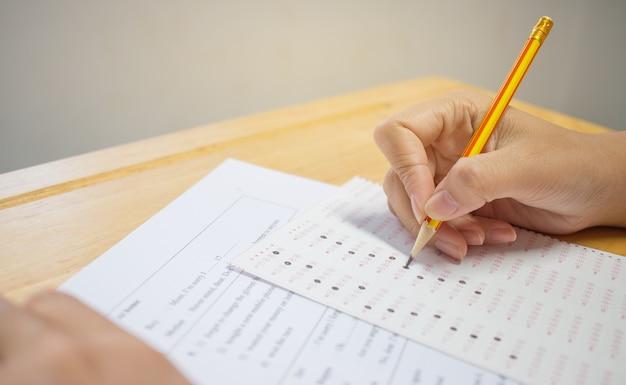 Mains d'étudiants prenant des examens, écrit la salle d'examen