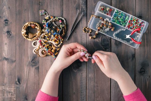 Mains faisant collier avec boîte de perles sur une vieille table en bois