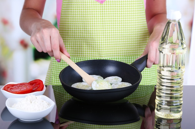Mains faisant cuire des courges dans la casserole dans la cuisine