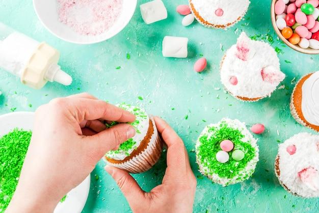 Mains faisant des cupcakes de pâques avec des oreilles de lapin