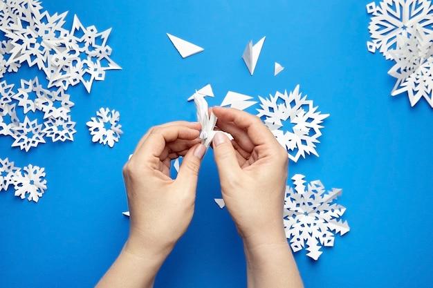 Mains faisant flocon de papier blanc sur bleu
