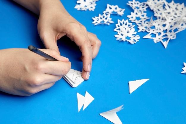 Mains faisant des flocons de neige en papier blanc sur bleu