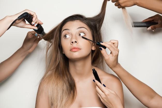 Mains faisant maquillage et coiffure de belle jeune femme