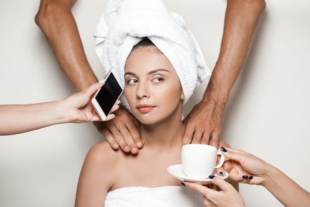 Mains faisant le massage, donnant le téléphone et le café à la belle femme