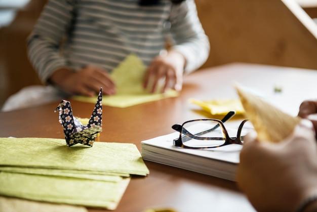 Mains faisant l'origami de cygne sur la table en bois
